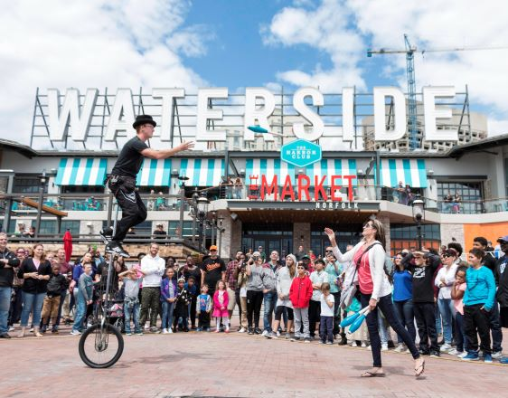 Waterside District after renovation. Man juggling and riding unicylce in front of a crowd.